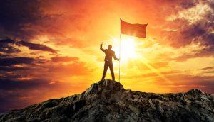 Geschäftsmann auf dem Gipfel eines Berges, in der Hand eine Fahne, im Hintergrund die untergehende Sonne
