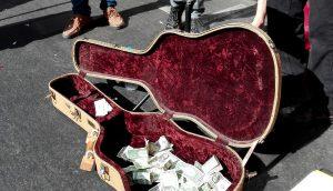 Der mit Dollarnoten gefüllte Gitarrenkoffer eines Straßenmusikers
