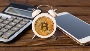 Kleiner Wecker mit Bitcoin zwischen Taschenrechner und Smartphone