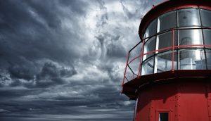Ein roter Leuchtturm vor einem wolkenverhangenem Himmel