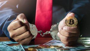 Mann in Handschellen, in der Linken hält er eine Bitcoin-Münze