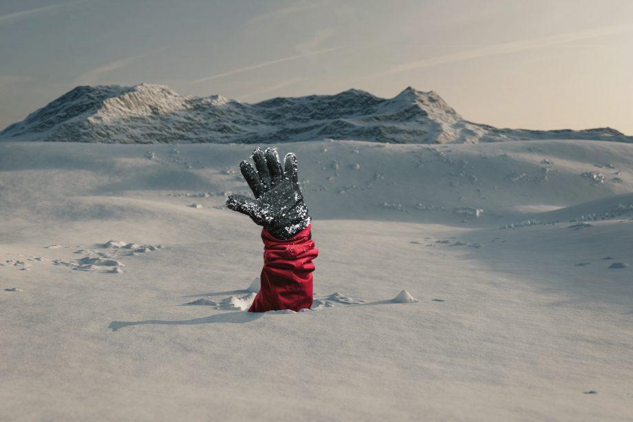 Der Arm eines Ski-Fahrers ragt aus einer Schneedecke