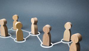 Eine Blockchain-Menschenkette aus Holzfigürchen.