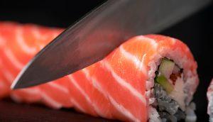 Zubereiten von Sushi zu Hause - Nahaufnahme von Händen, die eine Roll auf einem Board schneiden.