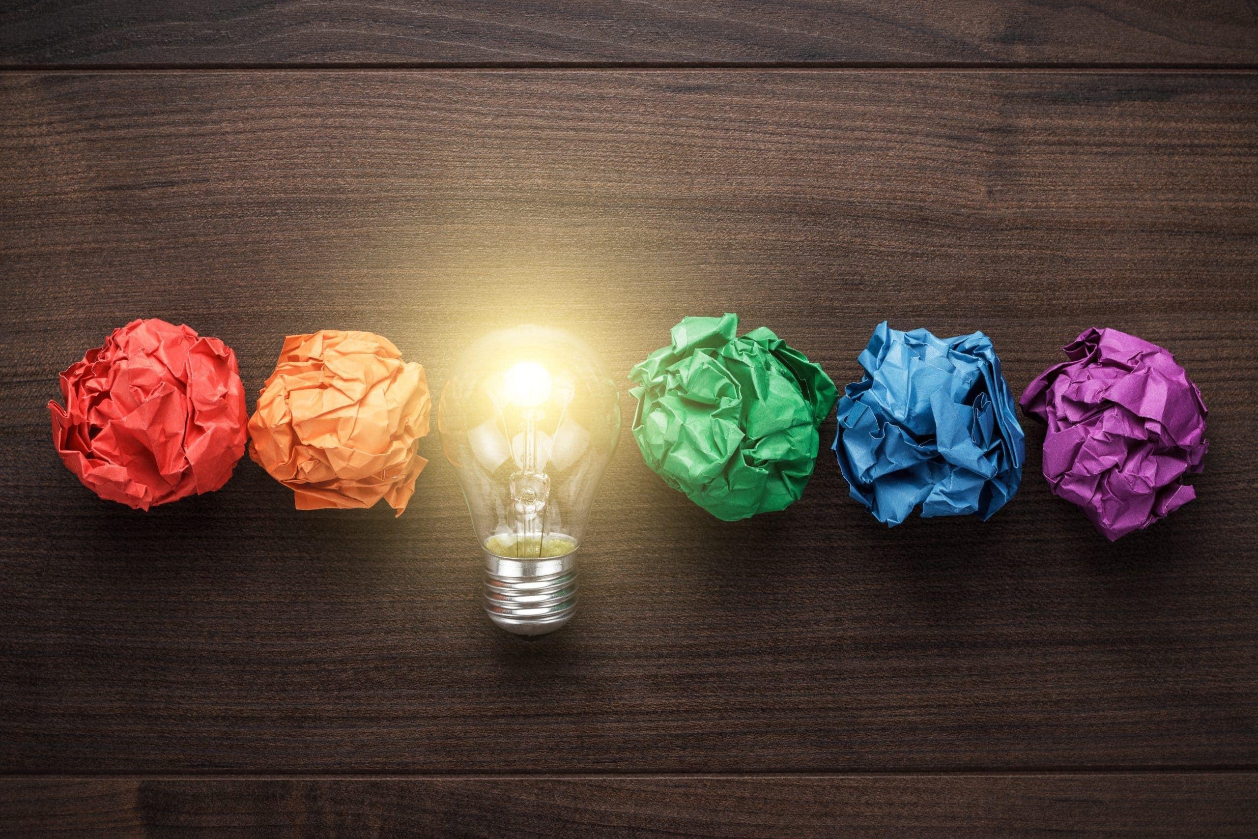 Eine Bitcoin-Glühbirne in mitten von buntem Papier.