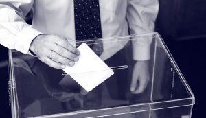 Ein Mann in Hemd und Krawatte steckt einen Zettel in eine transparente Wahlurne.