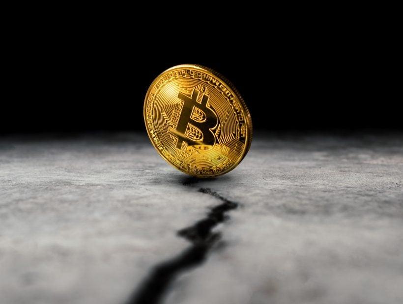 Bitcoin-Münze auf einem Spalt