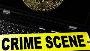 Bitcoin Münze auf dem Display eines Laptops, über dem ein Banner mit der Aufschrift Crime Scene liegt.