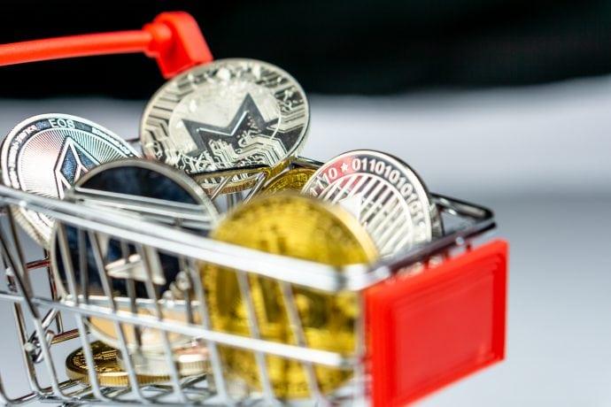 Ein Spielzeugeinkaufswagen mit Ethereum, Bitcoin und anderen Krypto-Münzen