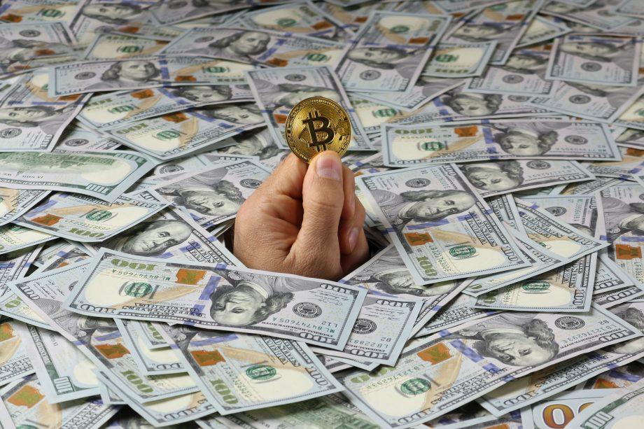 Aus einem Haufen Dollar-Noten ragt eine Hand, die eine Bitcoin-Münze hält
