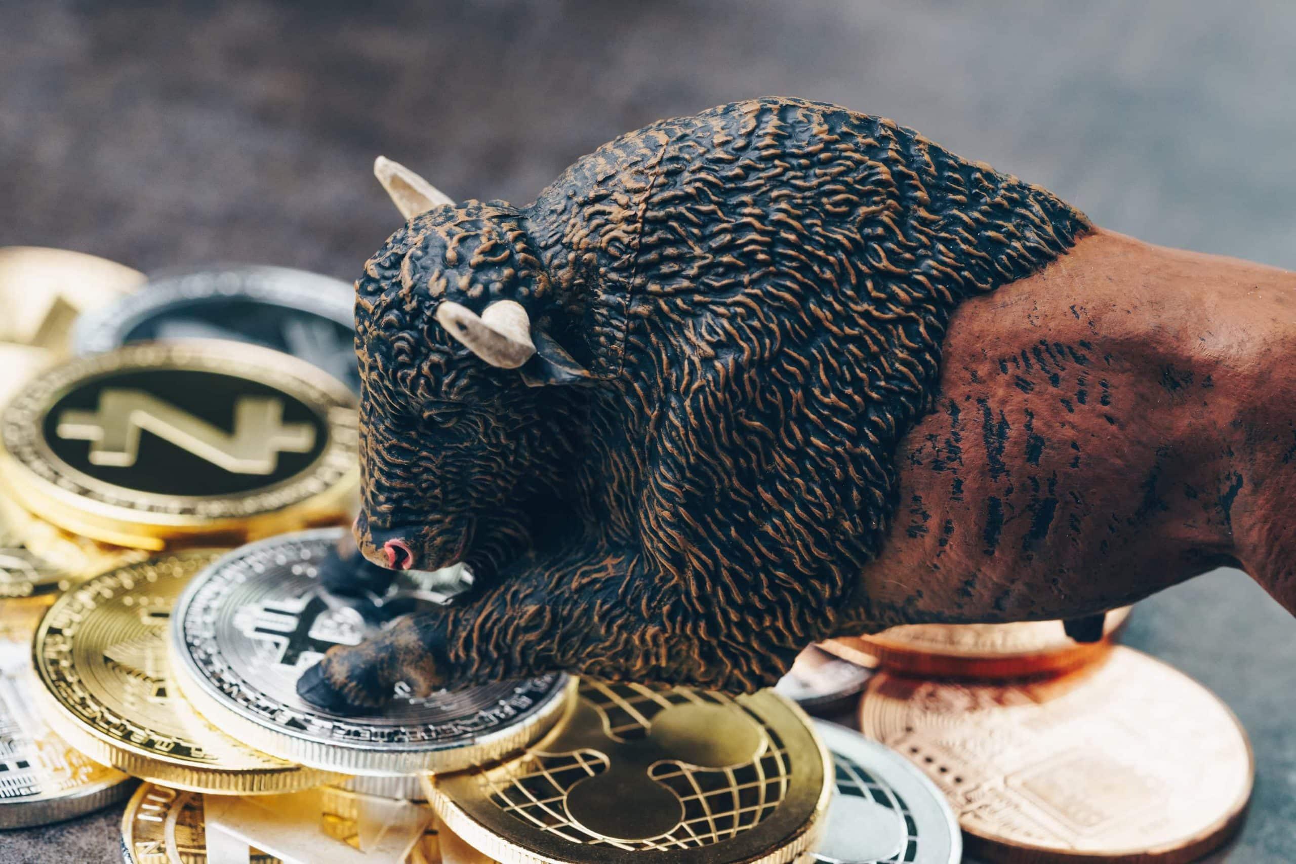 Eine Bullenfigur steht mit den Vorderläufen auf einem Stapel von Bitcoin- und Altcoin-Münuen