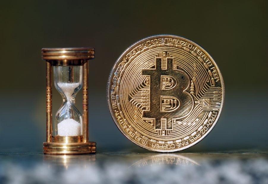 Bitcoin-Münze neben Sanduhr