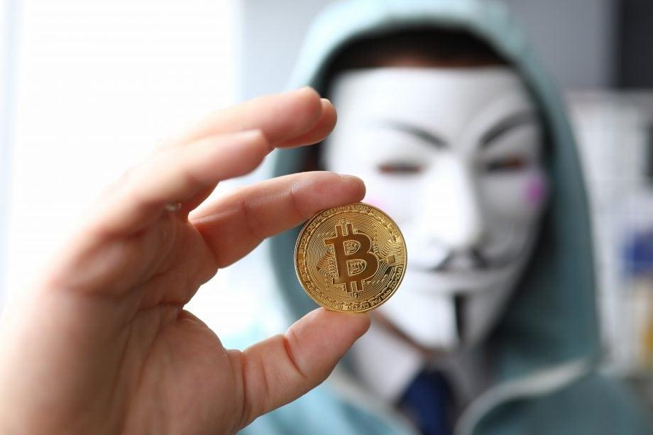 Bitcoin Münze wird von Menschen mit Maske hochgehalten.