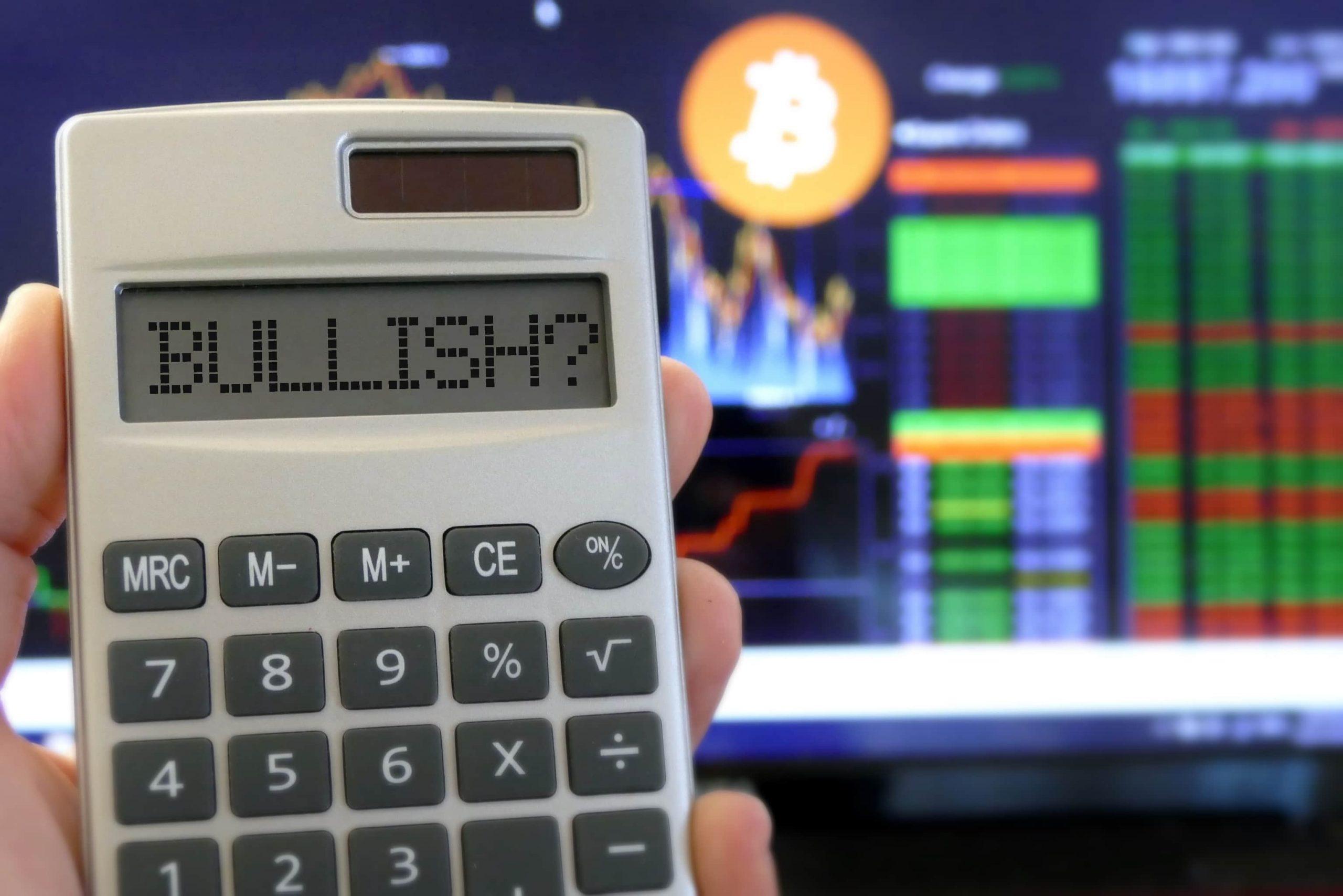 Taschenrechner mit Bullish Schriftzug und Bitcoin Chart im Hintergund
