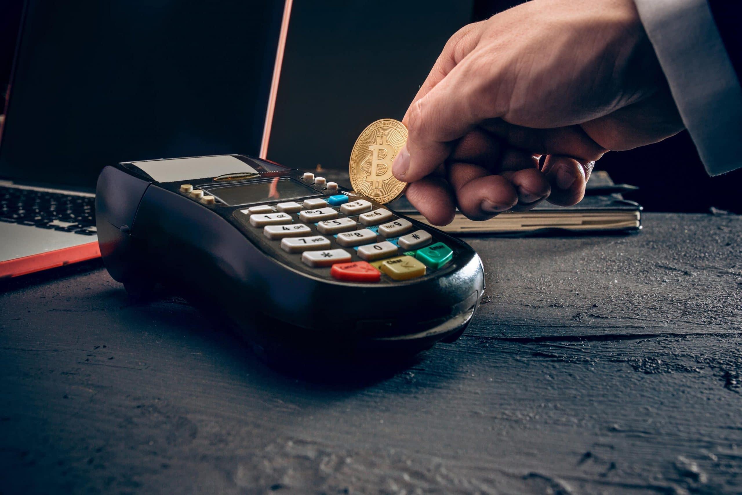 Ein Bitcoin wird wie eine Kreditkarte durch ein Kartenlesegerät gezogen