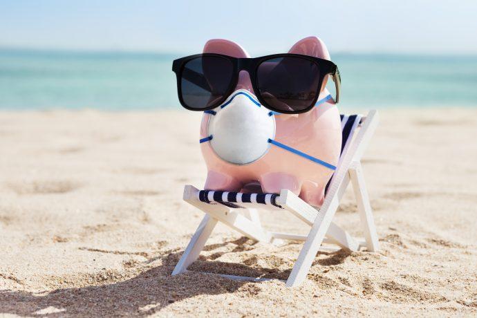 Ein Sparschwein mit Mund-Nasen-Schutz und Sonnenbrille auf einer Liege am Strand