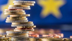 Schief gestapelte Euro-Münzen vor Europa-Flagge