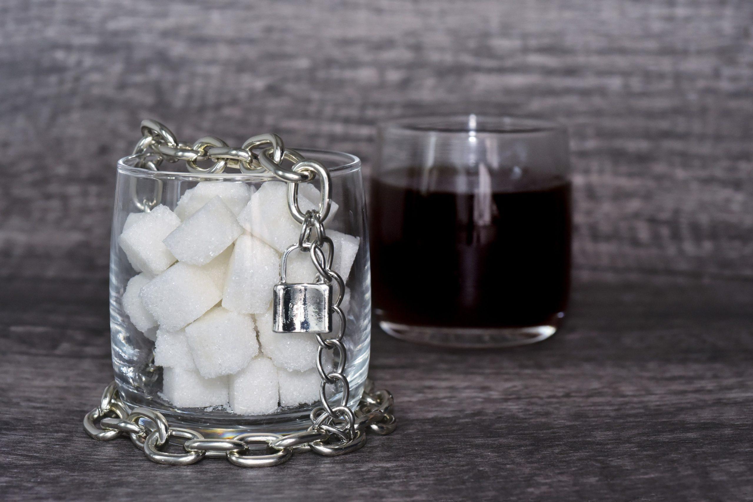 Ein mit Zuckerwürfeln gefülltes Glas mit Kette und Vorhängeschloss, dahinter ein Glas mit Kaffee