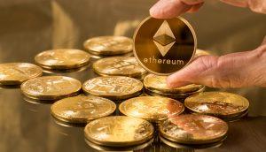 Eine Hand hält eine Ethereum-Münze vor einem Haufen Bitcoin-Münzen