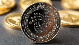 Eine IOTA-Münze, im Hintergrund weitere IOTA-Coins