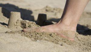 Ein Fuß zertritt eine Sandburg