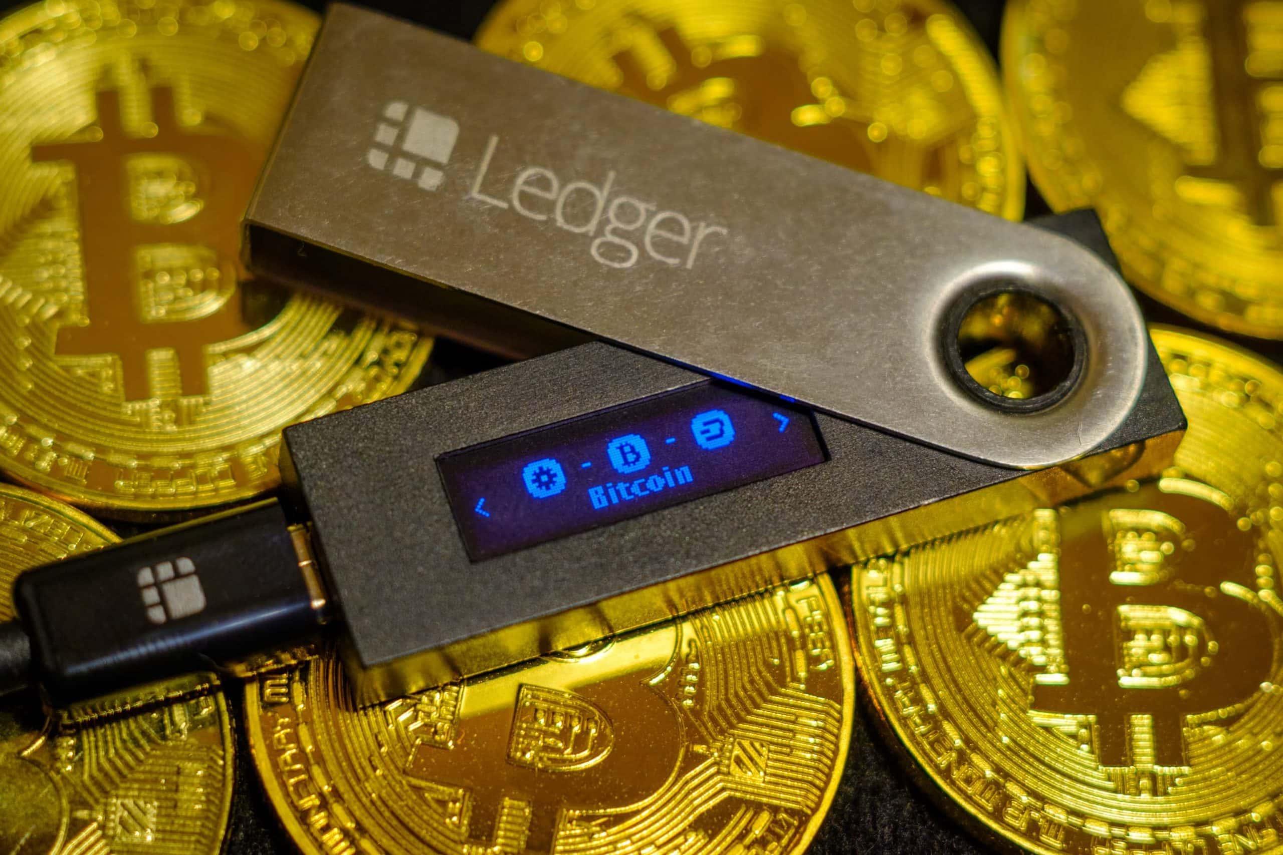 Eine Ledger-Hardware-Wallet liegt auf Bitcoin-Münzen