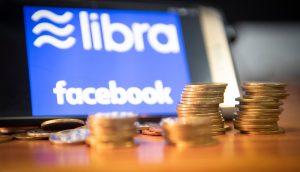 Mehrere Münzstapel, im Hintergrund ein Tablett mit den Logos von Libra und Facebook