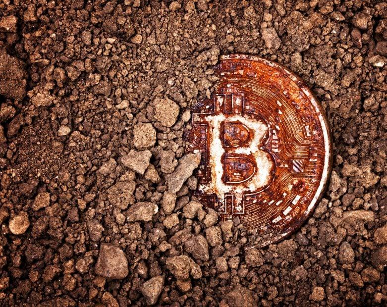 Halb verschüttete, rostige Bitcoin-Münze