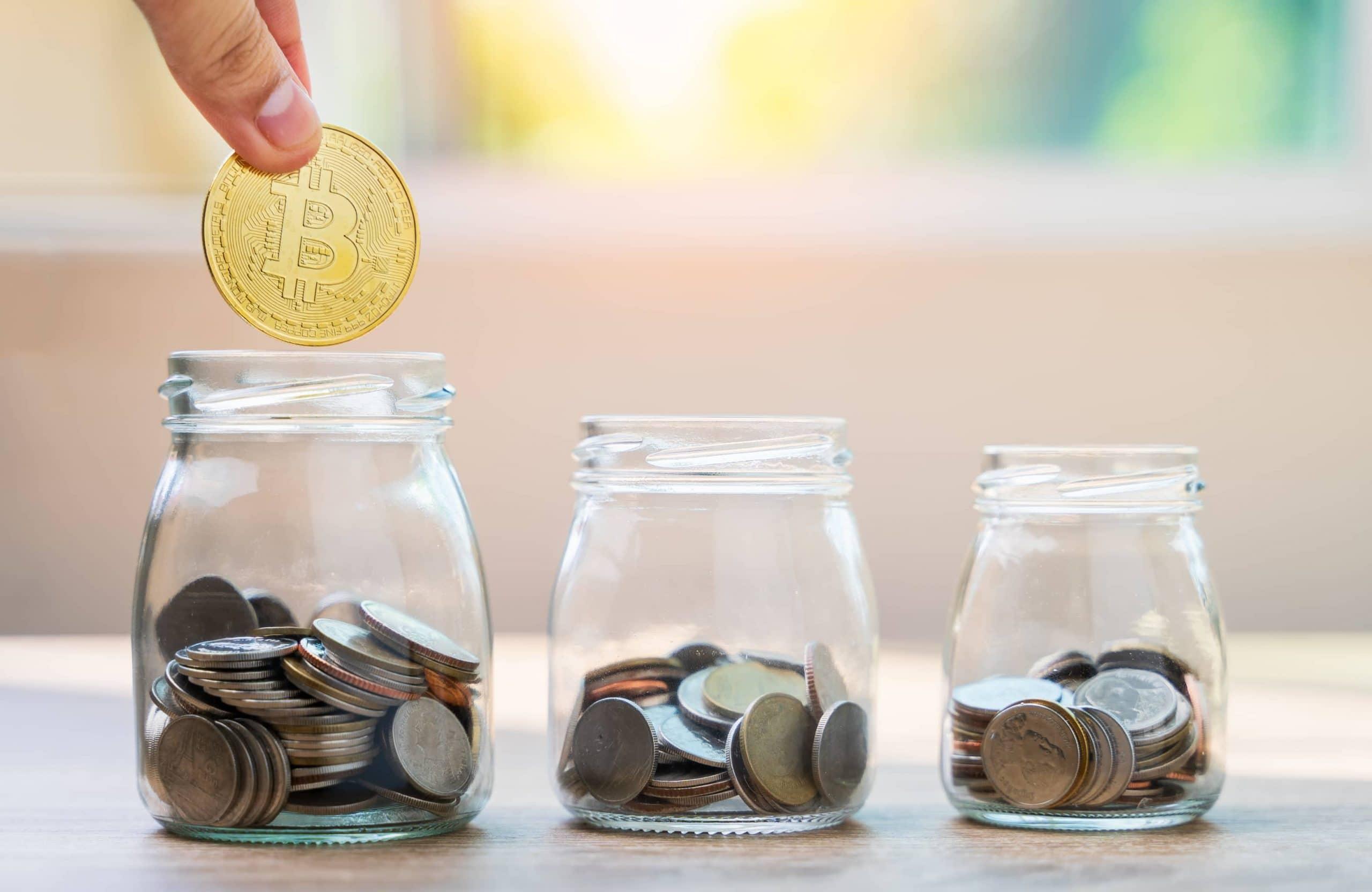 Mit Kleingeld gefüllte Gläser, in das größte wird eine Bitcoin-Münze gelegt