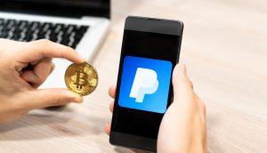 Ein Mann hält eine Bitcoin-Münze neben ein Smartphone mit PaypalLogo auf dem Bildschirm
