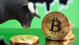 Bullenfigur neben Bitcoin-Münzen, im Hintergrund ein grüner Chart