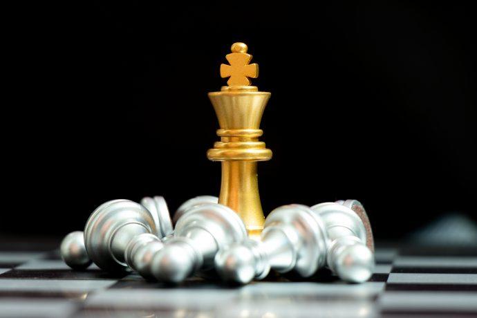 Goldener Schach-König umringt von silbernen Bauern, die auf dem Brett liegen