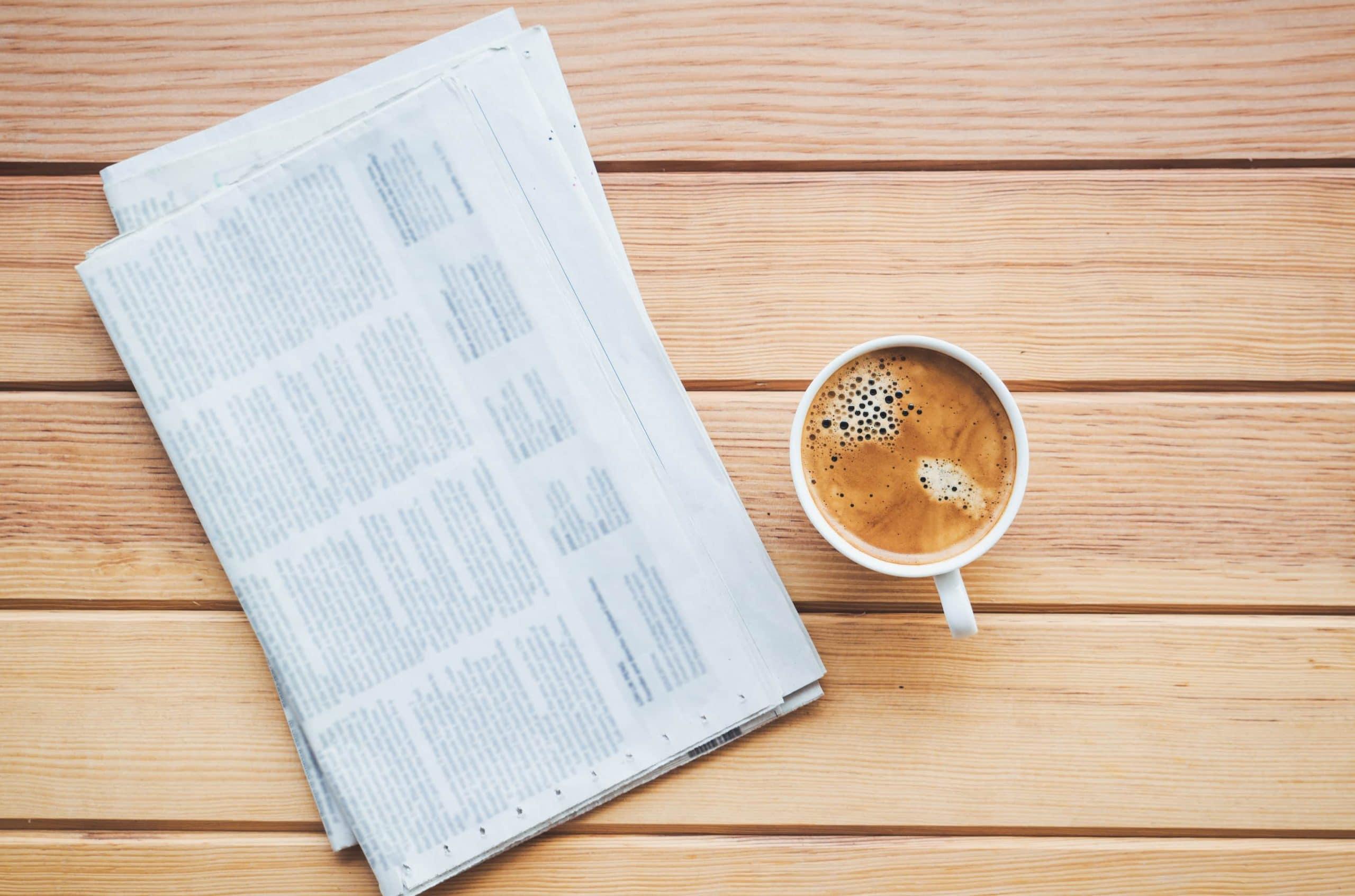 Eine Zeitung liegt zusammen mit einer Kaffeetasse auf einem Tisch.