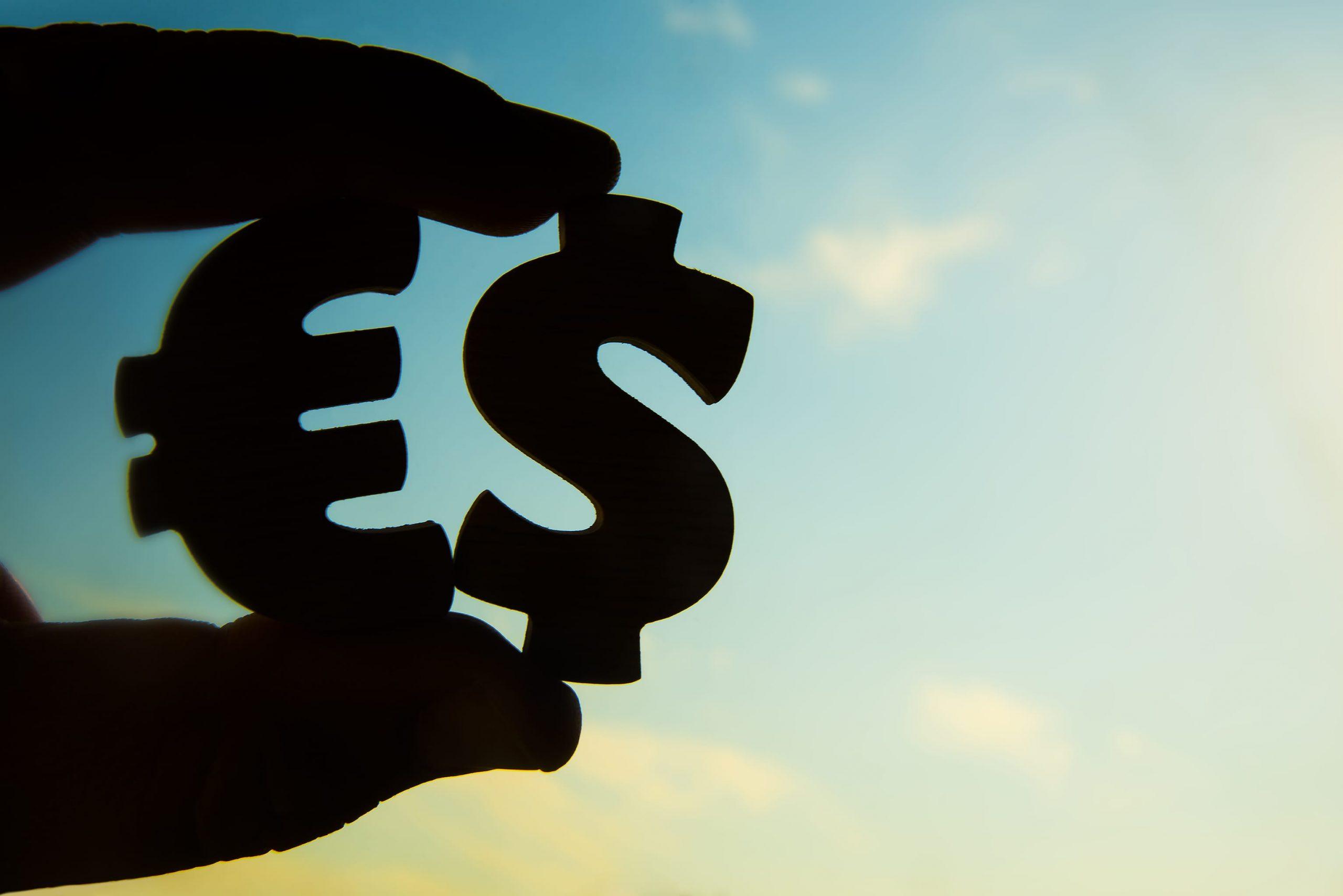 Im Gegenlicht fotographierte Aufnahme einer Hand, die ein Euro- sowie ein Dollar-Zeichen hält