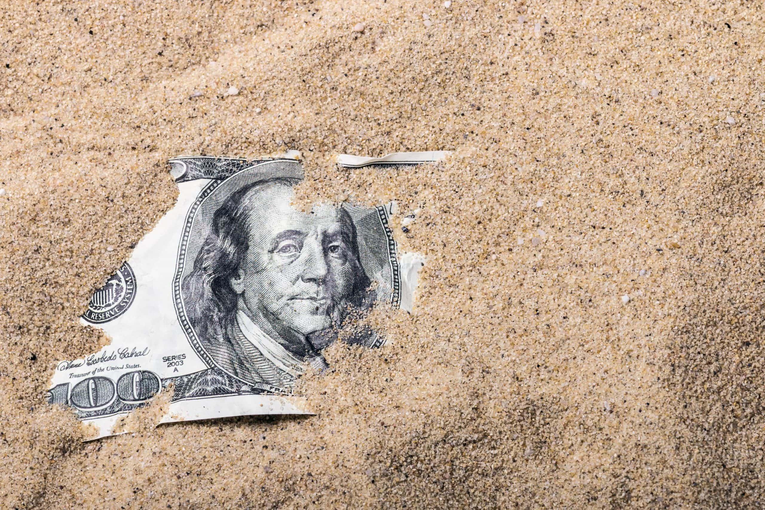 US-Dollar Note von Sand bedeckt