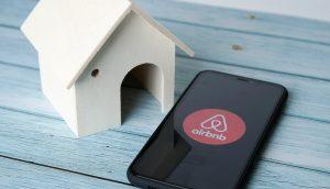 Smartphone mit Airbnb Logo liegt auf einem Tisch neben einem Miniaturhaus