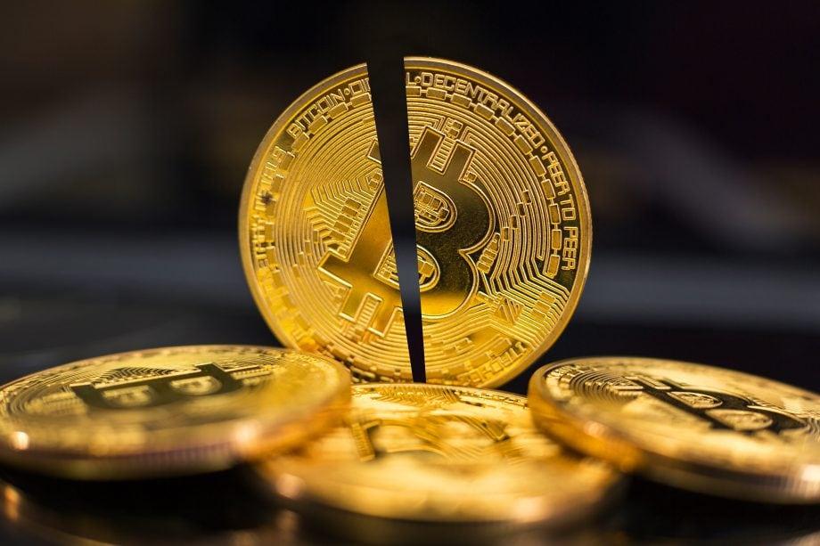 Halbierte Bitcoin-Münze auf schwarzem Hintergund