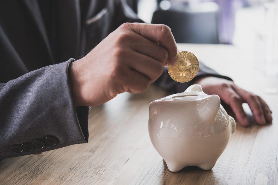 Person steckt Bitcoin-Münze in ein Sparschwein