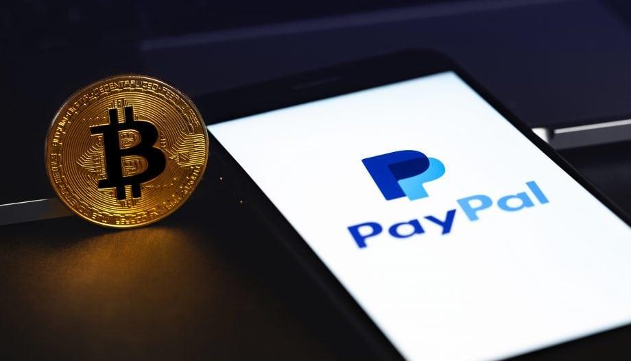 Bitcoin-Münze neben Smartphone mit PayPal-Logo