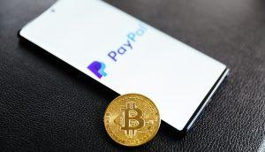 Paypal Logo auf Smartphone neben Bitcoin-Münze