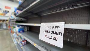 """Ein Zettel mit der Aufschrift: """"One per Customer"""", der an einem leeren Supermarktregal hängt."""