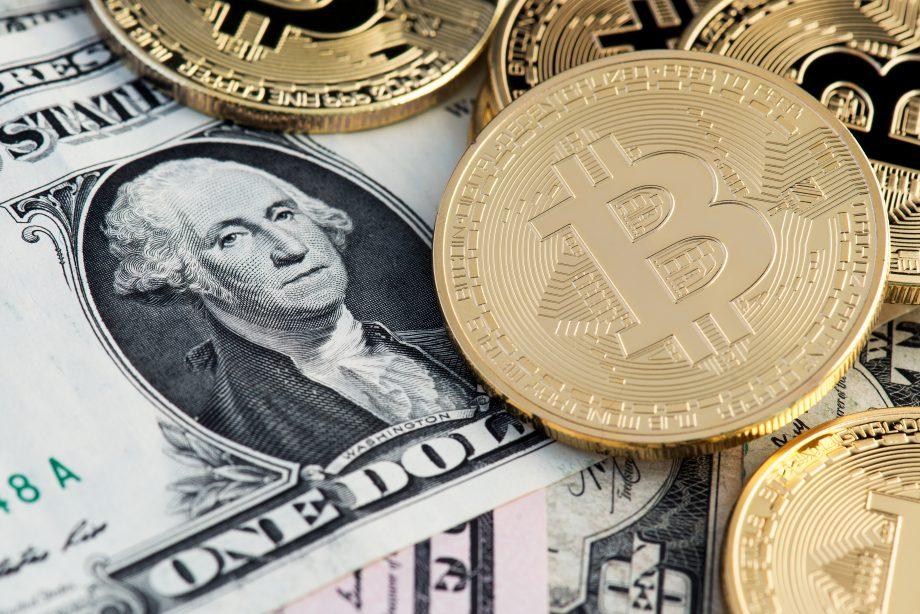 US-Dollar Banknoten sowie Bitcoin-Münze