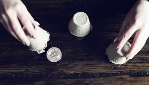 Eine Hütchenspielerin bewegt Becher über einer Bitcoin-Münze