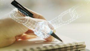 Eine Hand schreibt mit Kugelschreiber in ein Notizbuch