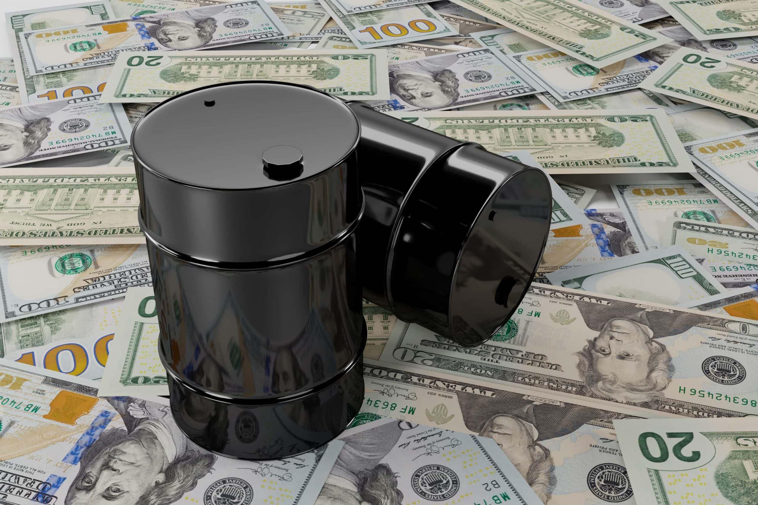 Zwei Miniatur-Ölfässer auf einem Haufen US-Dollar-Noten