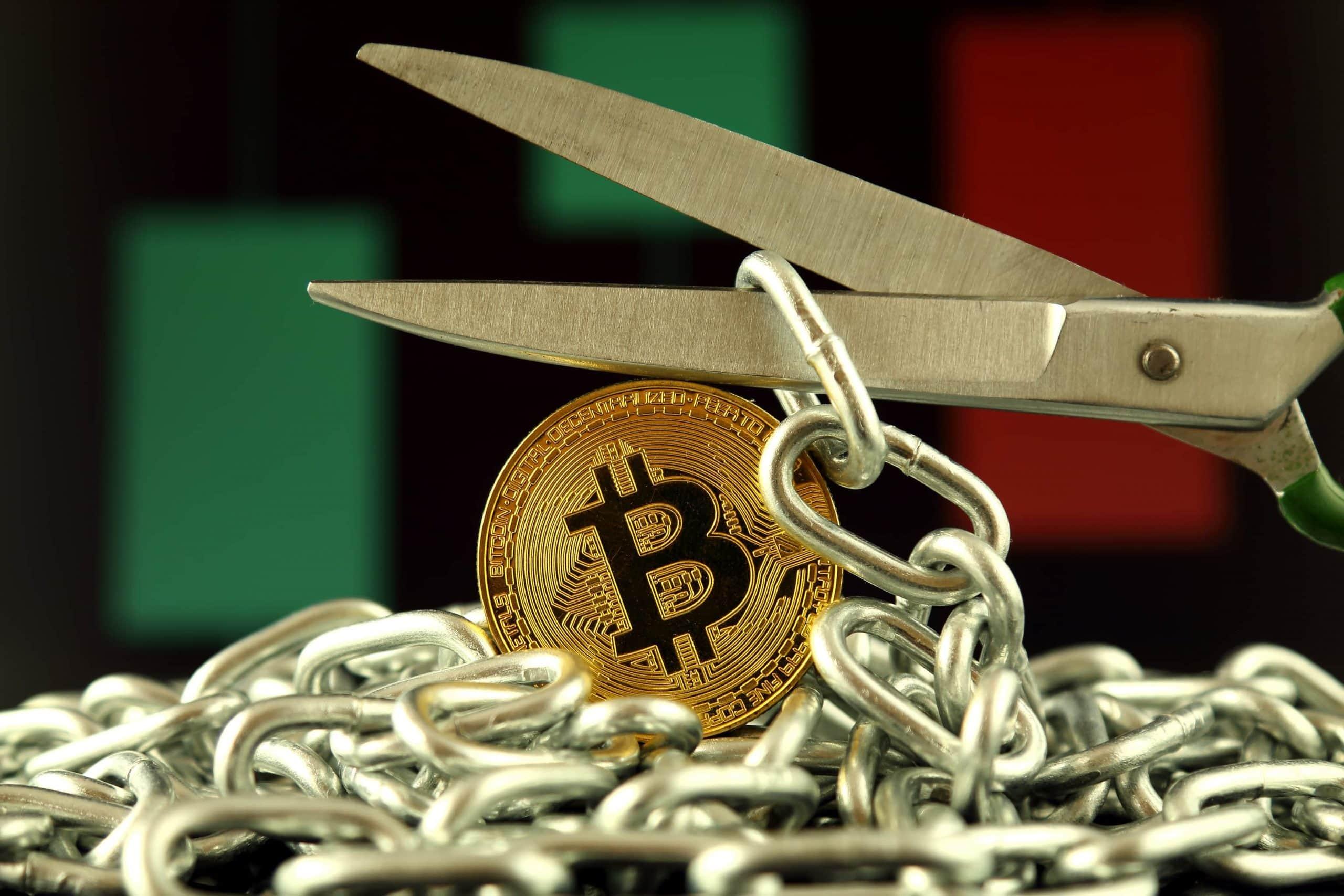 Schere durchtrennt eine Kette, darunter eine Bitcoin-Münze
