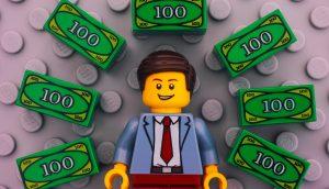 Lego-Männchen umringt von Lego-Geldscheinen auf grauer Bodenplatte