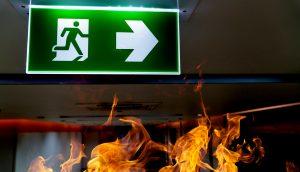 Exitschild zeigt den Weg aus den Flammen, was die deutsche Wirtschaft symbolisieren soll.