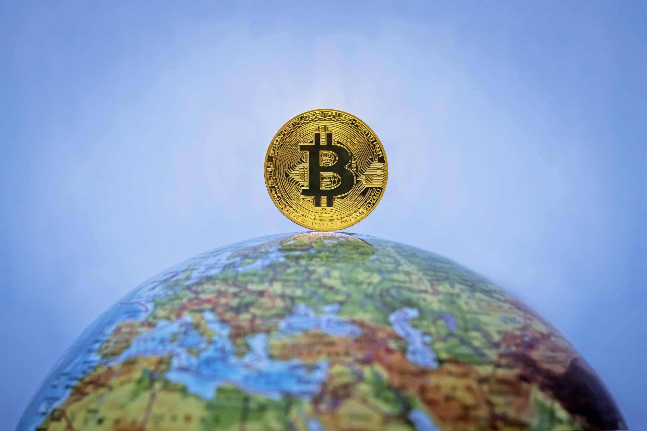 Bitcoin-Münze auf dem Nordpol eines Globus
