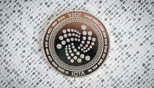 IOTA-Münze auf Papier, das mit Nullen und Einsen bedruckt ist